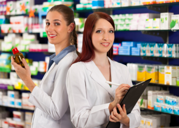 Two beautiful Nurses holding a medicine and a papers