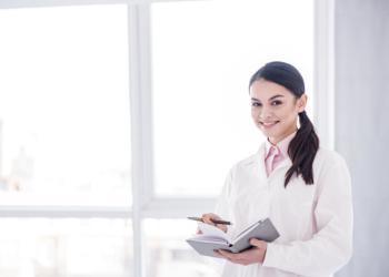 Nurse smiing holding a notebook